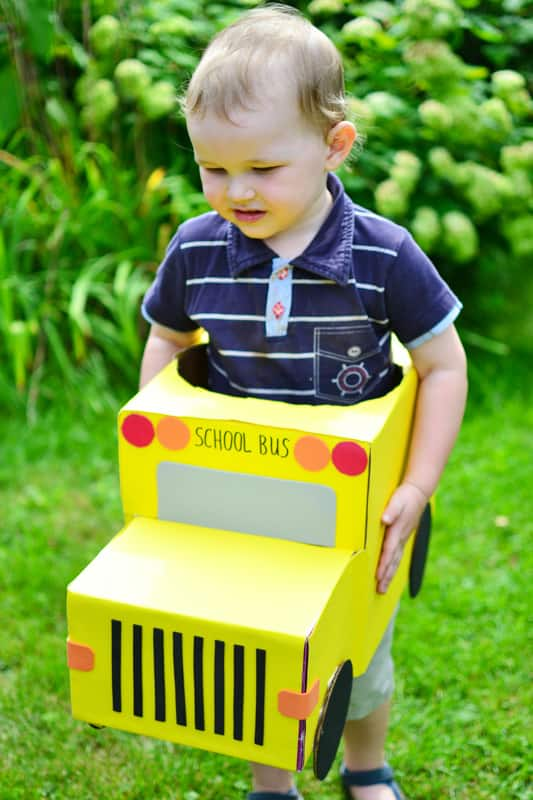 A boy plays with the cardboard box school bus.
