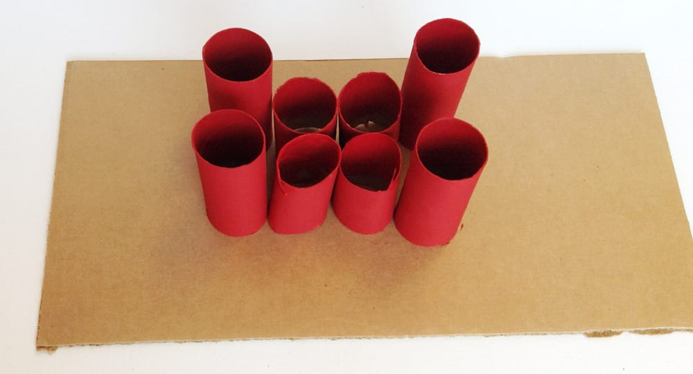 Toilet paper rolls painted red and arranged in the shape of a castle.