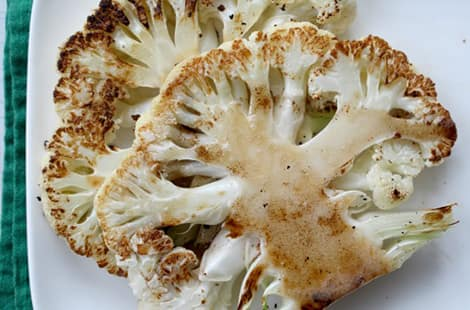 Cauliflower steaks on a plate.