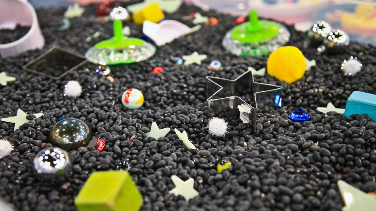 A bin filled with black beans, marbles, glow-in-the-dark stars, scoops, pompoms and magnets.