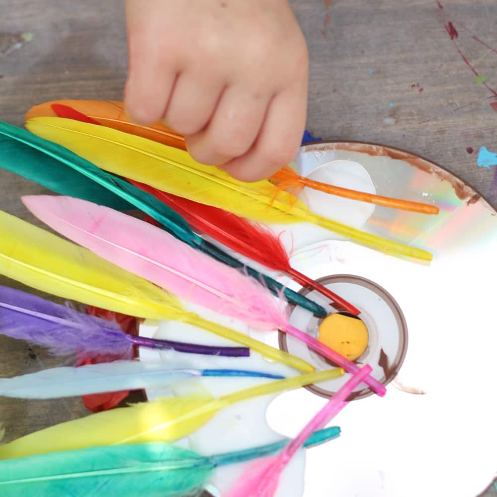A child glues feathers to the back of a CD.