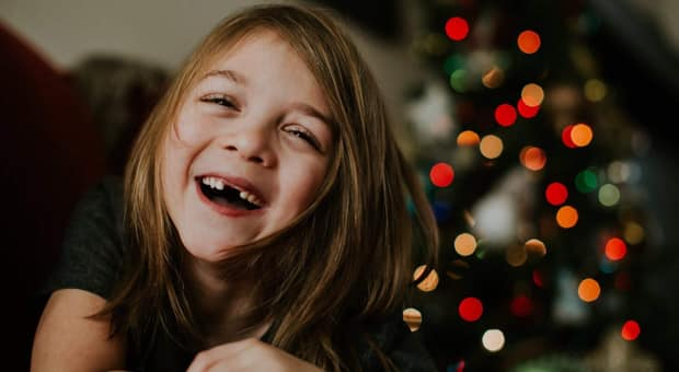 A young girl on Christmas morning smiles at her presents showing two missing front teeth
