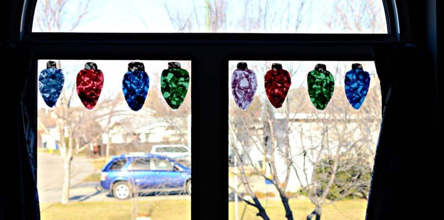 8 giant Christmas light suncatchers hanging in a window.