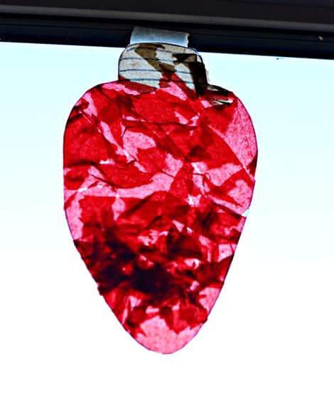 A single giant Christmas light suncatcher hanging in a window.