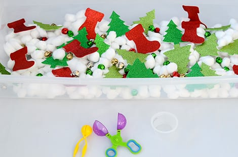 A bin filled with cotton balls, bells and glittery Christmas foam shapes.