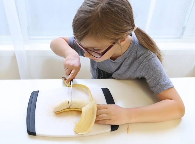 A child slicing a banana.