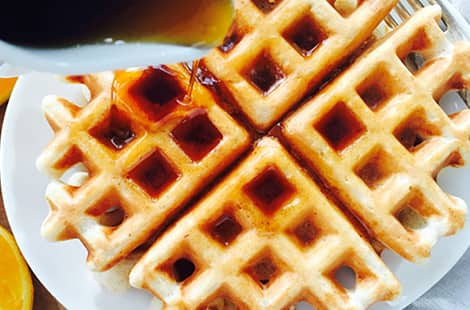 Maple syrup poured on waffle.