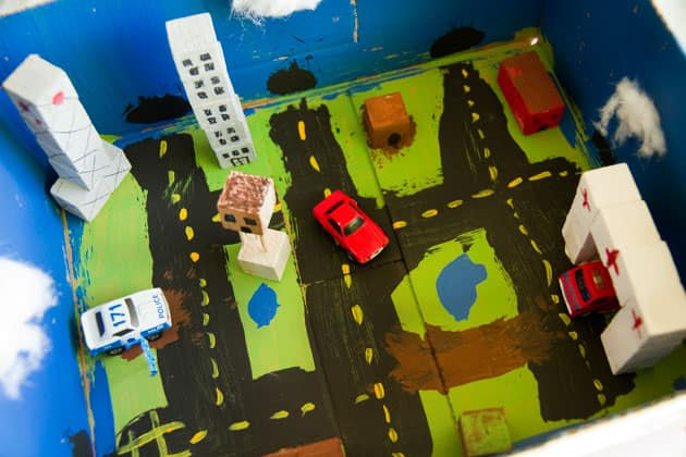 A completed box city, complete with buildings made from wooden blocks, cotton-ball clouds, painted roads and small cars.