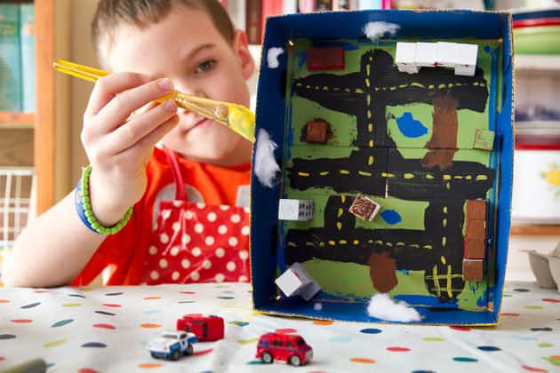 A view of the inside of a box city as a child paints the outside of the box.