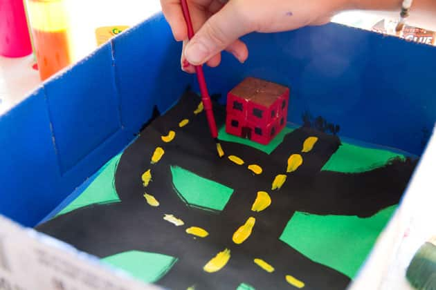 A child painting yellow lines on a road inside a box city.