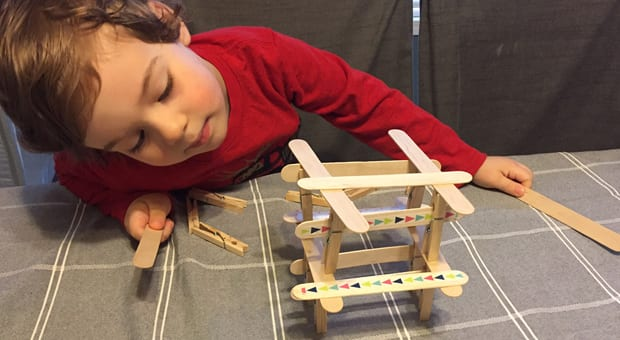 A young child builds a tower using craft sticks and clothespins