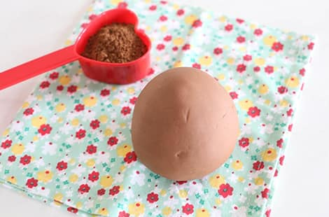 Chocolate play dough ball and a spoonful of cocoa powder.