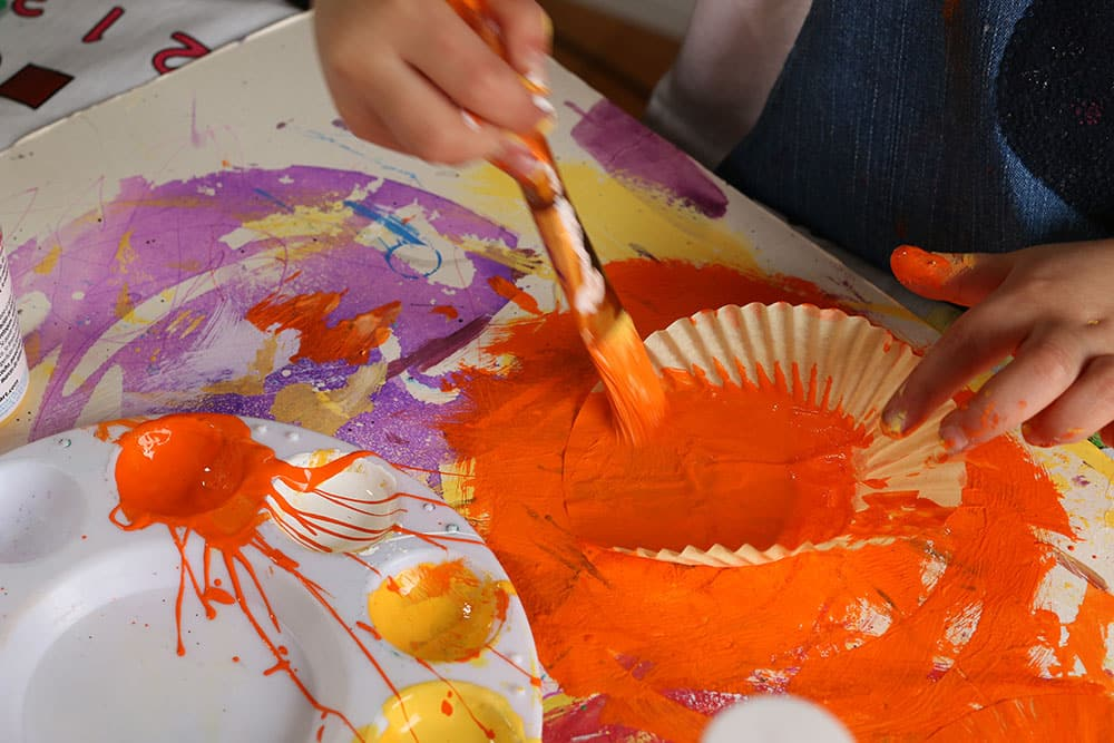 A cupcake liner being painted with orange craft paint.