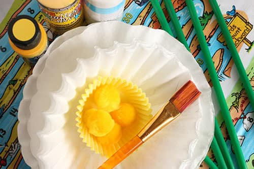 Needed supplies: craft paint, white frilly coffee filters, yellow cupcake liners, yellow pom-poms, green straws, paintbrushes.
