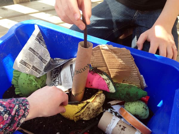 A child is dropping a rubber worm into a paper-towel tube inside of a bin filled with soil and
