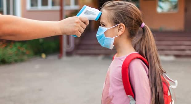 a child is having her temperature checked before being admitted inside a school