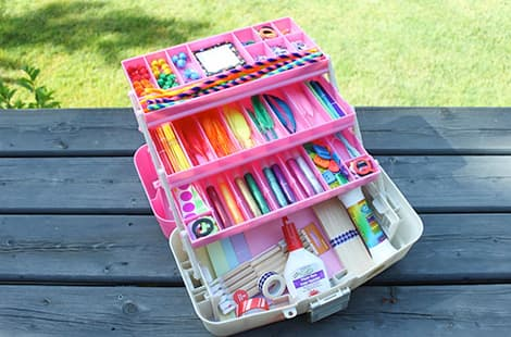 Pink tackle box with various craft materials — from sparkles to feathers to pom-poms — in the dividers.