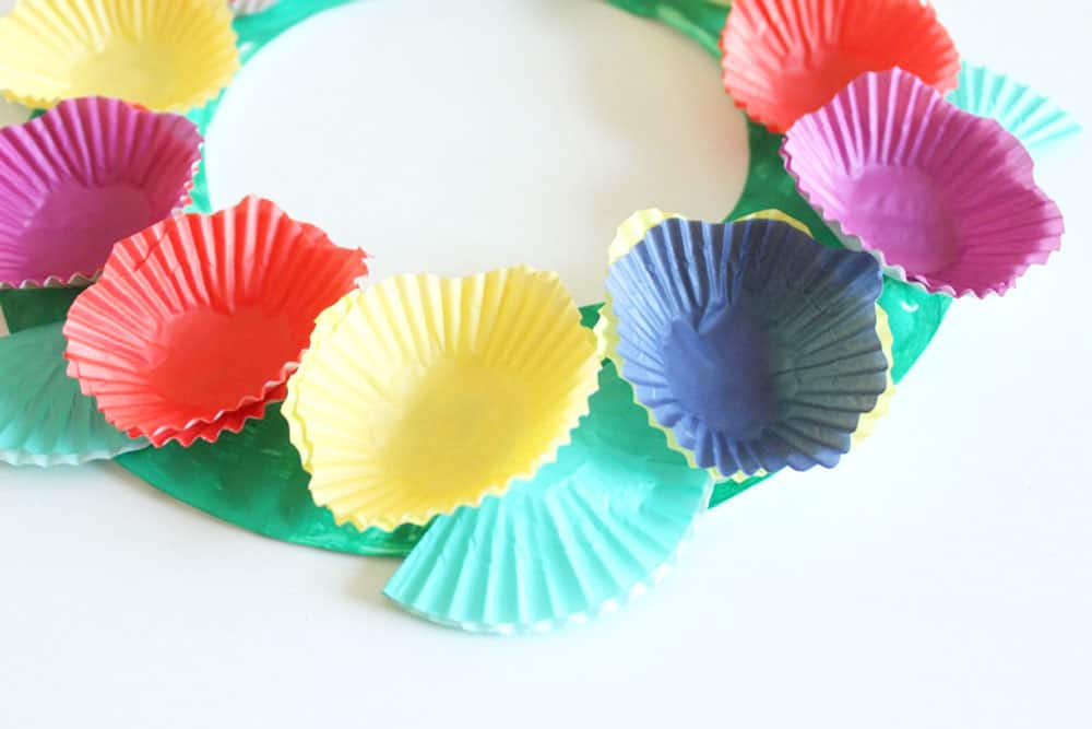A paper plate painted green, with cupcake liner flowers glued on top.