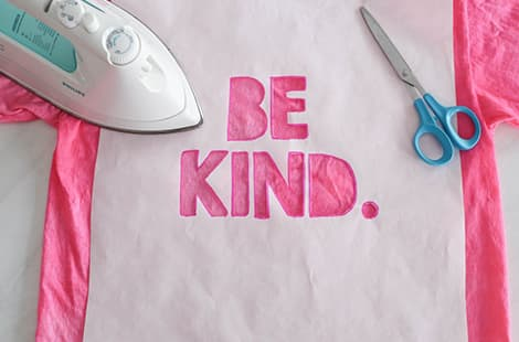 Be Kind letters cut out of stencil.