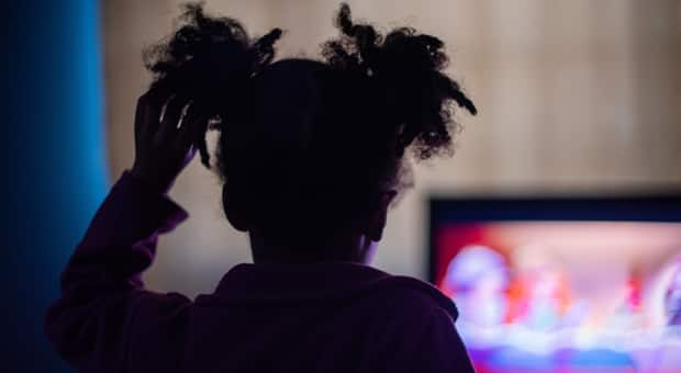 A young girl watching a movie in the dark