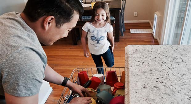 Dad loads dishwasher as daughter looks on