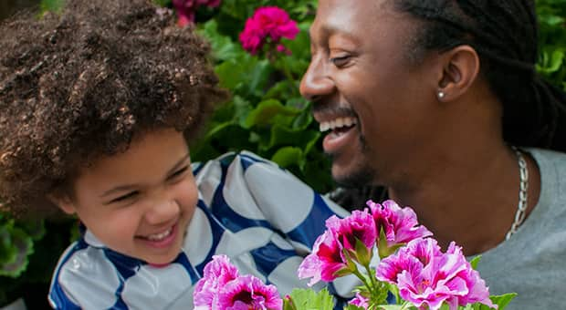 Dad and child in front of purple flowers