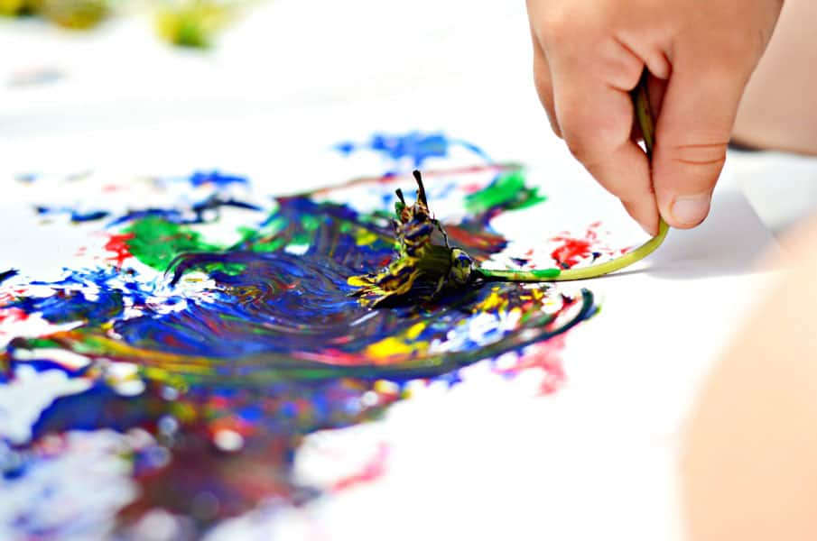 A child paints swirls of different colours with a dandelion paintbrush.