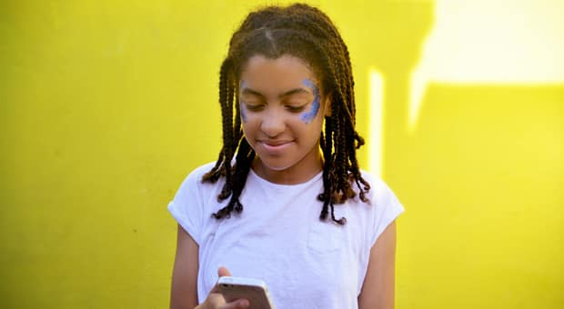 a young girl is looking at her phone