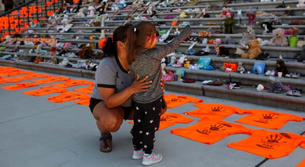 A child and her mother at a memorial of orange shirts in BC