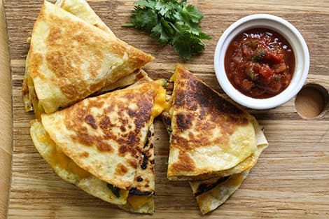 A platter of chicken quesadillas next to a bowl of salsa.