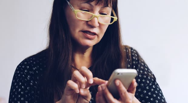 a mom looks closely at a phone