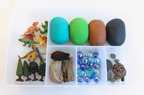 Plastic dinosaur toys, rocks, pieces of wood and different colour play dough.