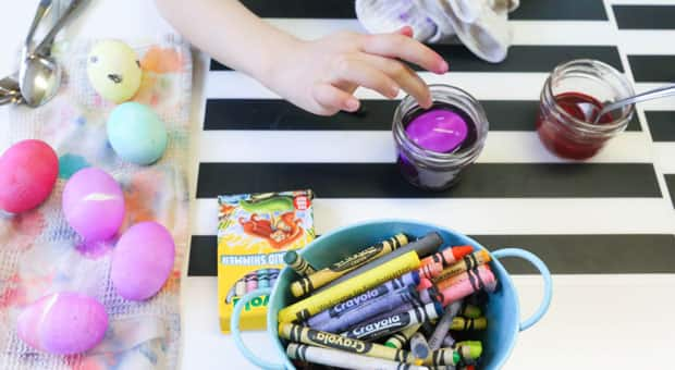 A table set out with all of the supplies needed to colour easter eggs.