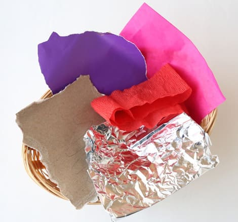A basket with torn pieces of coloured paper, crepe streamers, tissue paper, thin cardboard and tin foil.