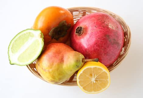 A basket of fresh fruit: persimmon, lime (halved), pear, pomegranate and lemon (halved).