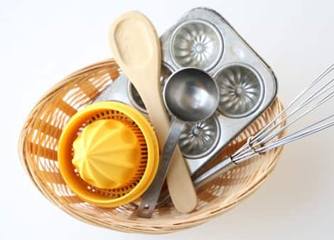 A basket with a wooden spoon, metal scoop, metal baking mould, plastic juicer and a whisk.