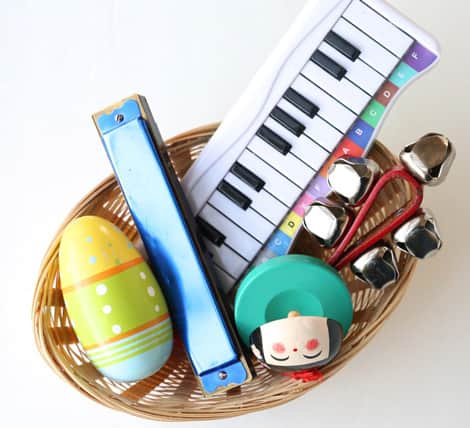Basket filled with small music-makers: a harmonica, mini keyboard, shaker, castanets and bells.