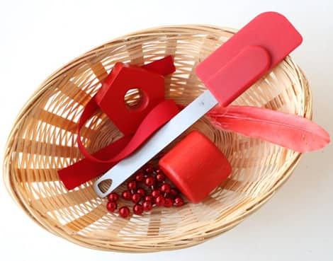 A basket of red things: a ribbon, wooden blocks, spatula, feather and a beaded necklace.