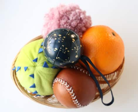 A basket filled with six different spherical objects: balls, oranges and pom-poms.