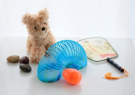 67de21120b9f River rocks, plastic slinky, stuffed toy, paper fan, silly putty all sitting