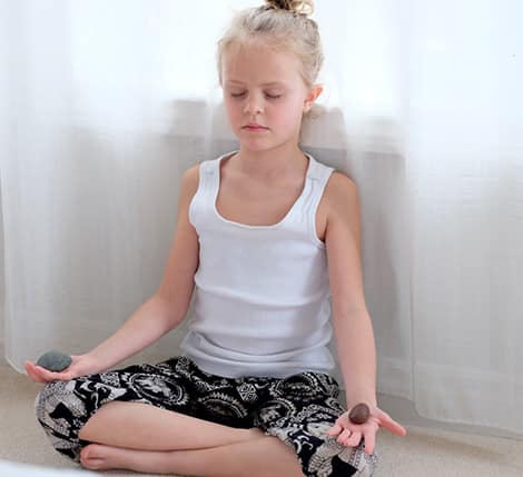 A child sitting with legs crossed and eyes closed with two river rocks in the palms of her hands.