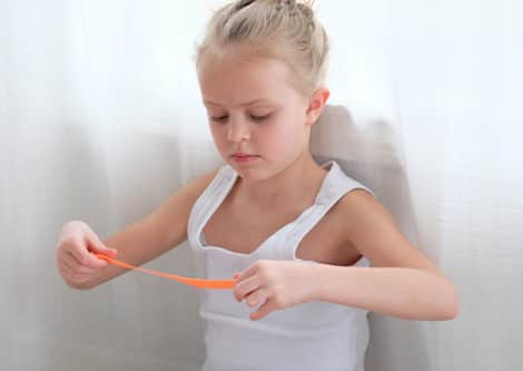 A child stretching out silly putty.