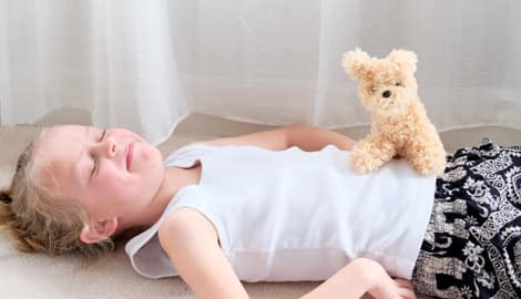 A child lying on the floor and laughing with a stuffed animal on her stomach.