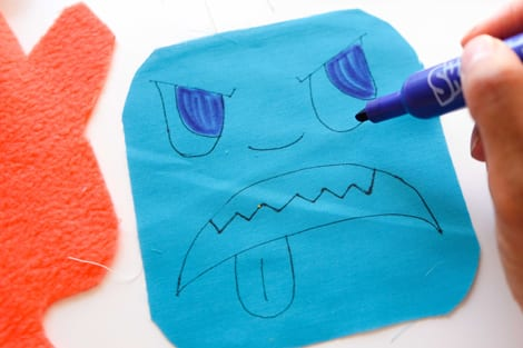 drawing monster face on piece of fabric