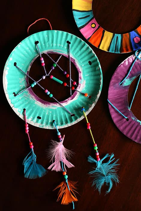 Colourful Rings Of Paper Plate Painted Bright Colours And Woven With Yarn Which Has Beads