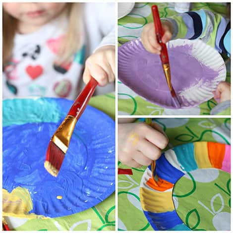 Children painting the rings of their plates with bright paint.
