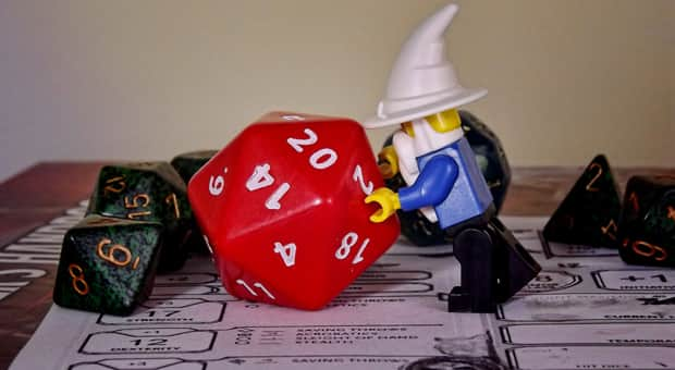 wizard statuette pushes a 20-sided die from Dungeons and Dragons