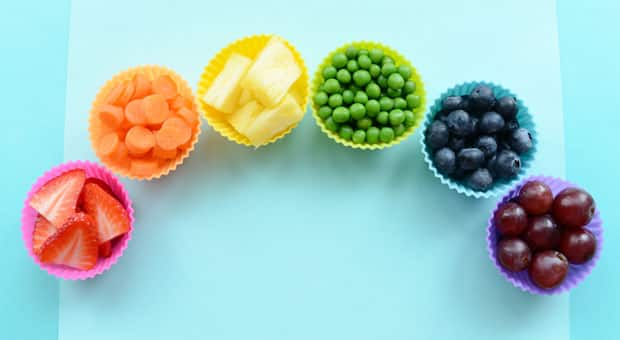 Strawberries, carrot coins, pineapple, green peas, blueberries and red grapes arranged in rainbow-coloured silicone muffin cups.