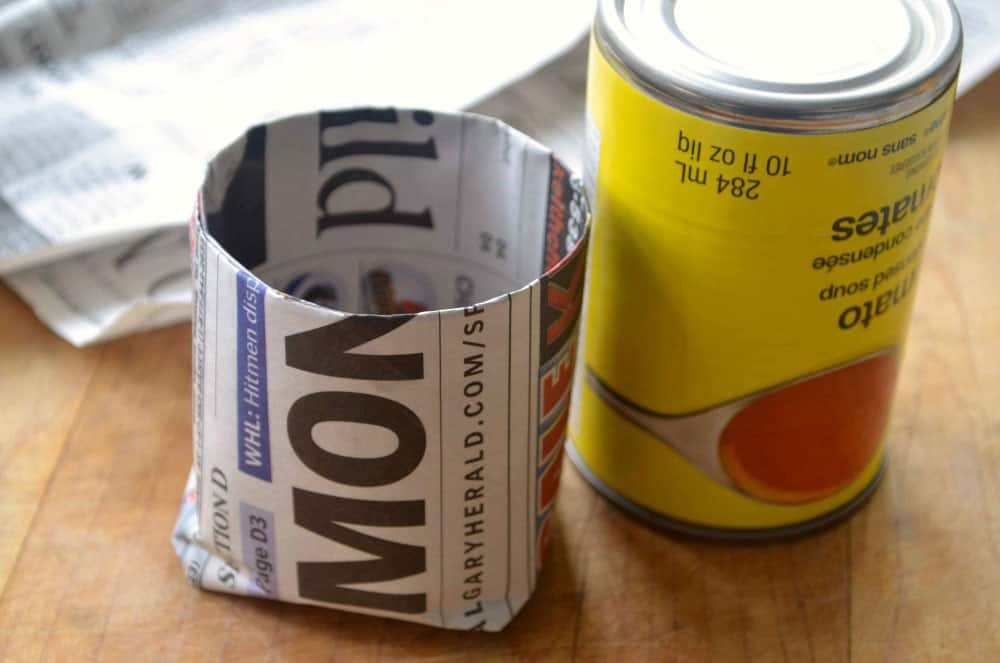 A small newspaper cup made by wrapping paper around the base of a small can.