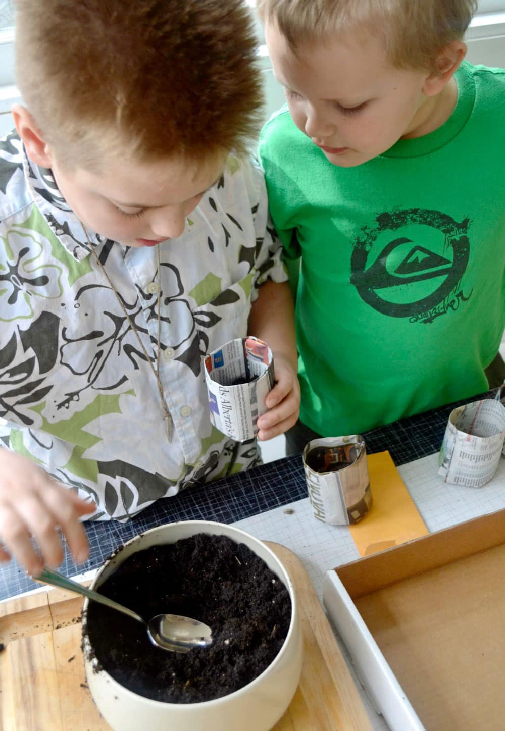 Two curious boys filling a newspaper cup with soil to prepare for seedlings.
